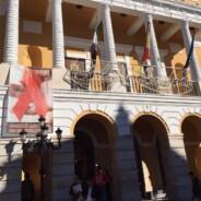 Un lazo rojo en la fachada del Ayuntamiento de Badajoz conmemora el Día Mundial contra el Sida